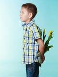 Pojkenederlagbukett av blommor bak honom Fotografering för Bildbyråer