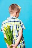 Pojkenederlagbukett av blommor bak honom Arkivfoto