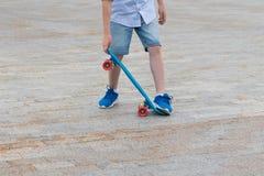 Pojkens ben lär att behandla en skateboard, närbild mot bakgrunden av vägen arkivfoton