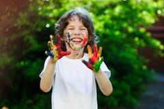 Pojkens framsida och händer i målarfärg arkivbild