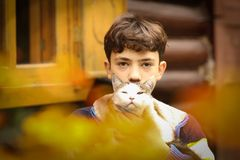 Pojkeomfamning med kattslut upp fotoet på sommarställehusräkning royaltyfria bilder