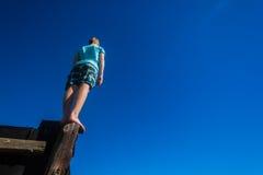 PojkePole anseende som balanserar himmel Arkivbilder