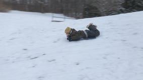 Pojkeridning på slädar i vintersnö arkivfilmer