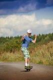Pojkeridning på vägwaveborden Arkivfoto