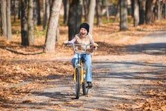 Pojkeridningen på cykeln i höst parkerar, den ljusa soliga dagen, stupade sidor på bakgrund Royaltyfria Bilder
