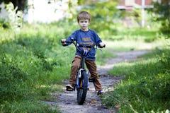 Pojkeritt som en cykel i stad parkerar Royaltyfri Foto