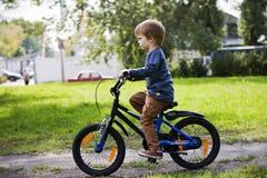 Pojkeritt som en cykel i stad parkerar Arkivfoto