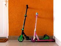 Pojkes och flickas lilla färgrika sparkcyklar som lutar mot stuckaturväggen bredvid den vita ingångsdörren arkivfoto