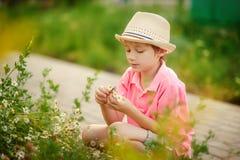 Pojkesammanträde i blommorna Arkivfoto