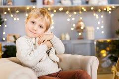 Pojkesammanträde i stol på bakgrund av jullandskap Fotografering för Bildbyråer