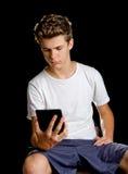 Pojkesammanträde med ebookavläsaren eller minnestavlan i hans hand Arkivfoto