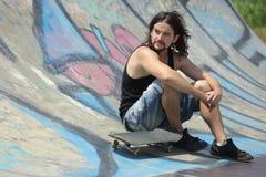 Pojkesammanträde med en skateboard på ett halvt rör fotografering för bildbyråer