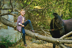 Pojkesammanträde på det gamla trädet som poserar med en häst efter en genomkörare Fokusera på pojken Royaltyfri Bild