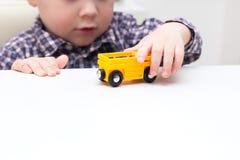 Pojkesammanträde på en tabell och spela med det hemmastadda drevet fotografering för bildbyråer