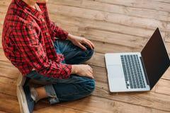 Pojkesammanträde på golv med den digitala bärbara datorn Arkivbild