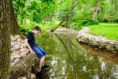 Pojkesammanträde på kanten av strömmen som får skor våta Arkivbild