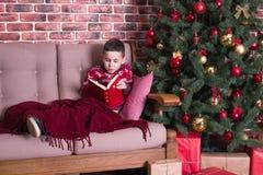 Pojkesammanträde på stol och läsning en bok Arkivfoton