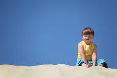 pojkesanden sitter royaltyfri fotografi