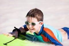 Pojkesimning på boogiebräde Arkivfoto