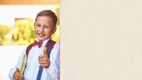Pojkeskolpojken som rymmer en lärobok som lutar mot väggen av skolan, visar ett handtecken av godkännande som lyfter hans finger  arkivfoto