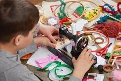 Pojkeskräddaren lär att sy, jobbet - handgjord och hemslöjdbegrepp för utbildning, royaltyfri bild