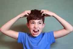 Pojkeskrapa hans huvud som isoleras på blått Arkivbild