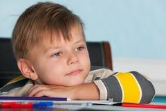 pojkeskrivbord little som är fundersam arkivfoto