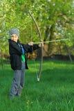 Pojkeskytte med en hand - gjord pilbåge och pil Arkivfoton