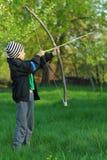 Pojkeskytte med en hand - gjord pilbåge och pil Royaltyfri Foto