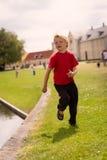 Pojkespring förbi vattenkanten Arkivbild