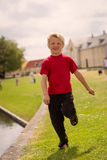 Pojkespring förbi vattenkanten Arkivbilder