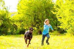 Pojkespring i väg från hund eller doberman i sommar Royaltyfri Foto
