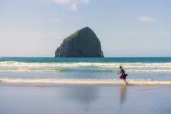 Pojkespring på att le för strand royaltyfri bild