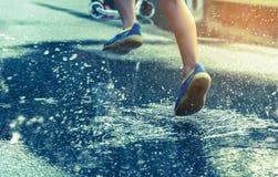 pojkespring på den våta gatan arkivbild