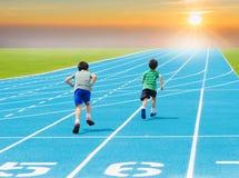 Pojkespring på löparbana Arkivbild