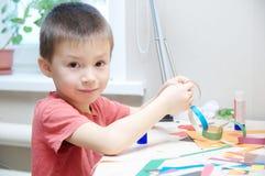 Pojkestående som spelar med papper, barn som tillverkar aktivitet royaltyfri bild