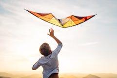 Pojkestart som flyger den ljusa orange draken i himlen royaltyfri fotografi
