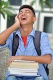 PojkestudentAnd Laughter With böcker royaltyfri foto