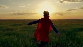 Pojkesuperhero i ett fält på solnedgången
