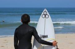 Pojkesurfaren ser vågor Arkivfoton