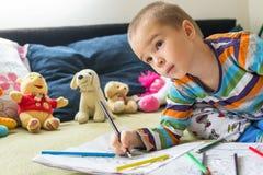 Pojketeckning för litet barn med färgblyertspennor Royaltyfri Bild