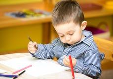 Pojketeckning för litet barn med färgrika blyertspennor i förträning på tabellen i dagis Arkivfoto
