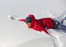Lycklig pojketonåring i snowen Arkivfoto