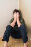 Pojketonåring med fördjupningssammanträde i hörnet av rum Royaltyfri Fotografi