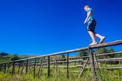Pojketonåring som går balansera staketet  Royaltyfria Foton