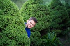 Pojketonåring som kikar ut ur en buske royaltyfri bild