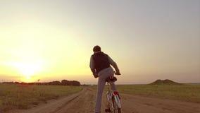 Pojketonåring som rider en cykel Pojketonåringen som rider en cykel, går till naturen längs den videopd rörelsen för banasteadica Royaltyfria Bilder