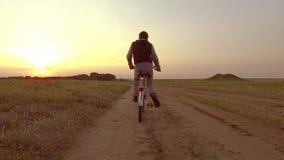 Pojketonåring som rider en cykel Pojketonåringen som rider en cykel, går till naturen längs den videopd rörelsen för banasteadica Royaltyfria Foton