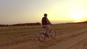 Pojketonåring som rider en cykel Pojketonåringen som rider en cykel, går till naturen längs för steadicamskottet för banan den vi Royaltyfri Foto