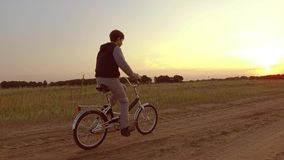 Pojketonåring som rider en cykel Pojketonåringen som rider en cykel, går till naturen längs för steadicamskottet för banan den vi Arkivbild